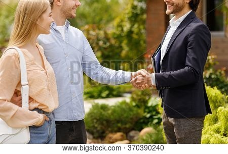 Cropped View Of Real Estate Broker Shaking Hands With His Clients, Closing House Rental Deal Outside