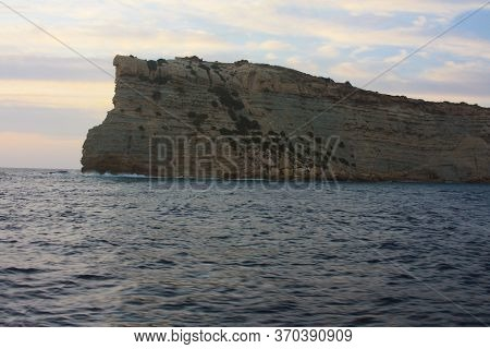 Rocky Cliffs In The Blue Waters Of The Ocean In The Middle Of The Ocean And Blue Sky