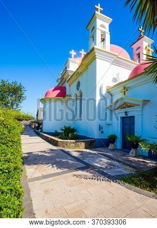 Israel. Capernaum. Church of the Twelve Apostles. Snow-white church building with pink domes and golden crosses. Place of worship and pilgrimage. The concept of religious pilgrimage and photo tourism