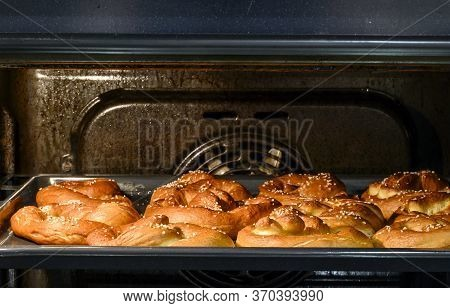 Cooking Pretzel In The Home Kitchen In The Oven. Pretzel With Salt On A Baking Pan Ready For Baking.