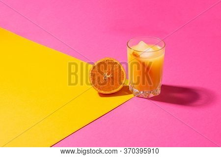 A Glass Of Orange Juice With Ice And Half An Orange On A Bright Yellow-pink Background. Freshly Sque