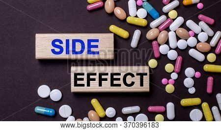 Side Effect - Words On Wooden Printed Blocks Between Multi-colored Tablets On A Dark Background