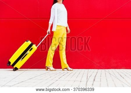 Woman With A Yellow Suitcase Walking Down The Street
