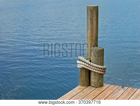 The Corner Of A Boat Dock, On A Lake, With Rope Wrapped Around Pilings.