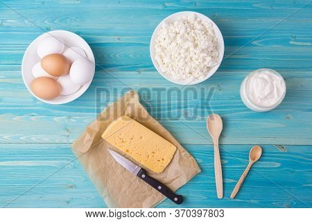 The Knife Is Lying On A Piece Of Paper Near The Cheese. Fresh Cottage Cheese, Sour Cream And Eggs In