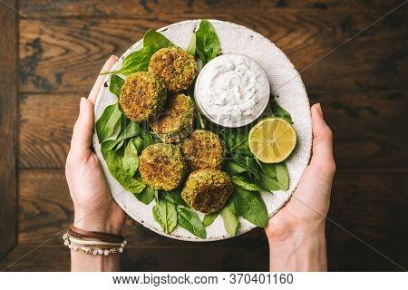 Falafel With Yogurt Tzatziki Dip Sauce. Womans Hands Holding Plate Of Vegetarian Spinach Falafel Ser