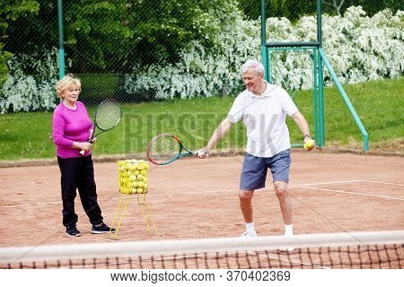 Full Length Shot Of Senior Man Teaching Elderly Woman Playing Tennis On The Tennis Court.
