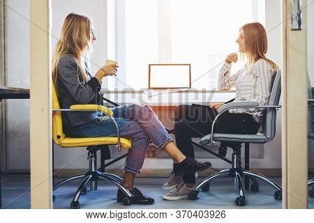 Women Coworkers Sitting In Coworking Office Near Computer With Mock Up Screen