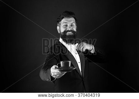Art Of Serving Tea. Happy Waiter Serve Tea Black Background. Bearded Man Give Cup Of Tea. Breakfast