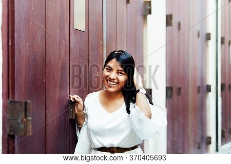 Long-haired Latina Woman In White Dress Smiling At Camera Leaning Against Wooden Wall. Lifestyle Con