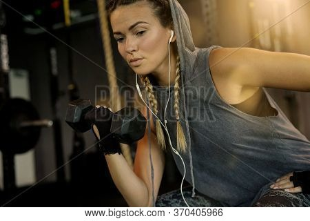 Woman in a gym working out, lifting weights and listening to music