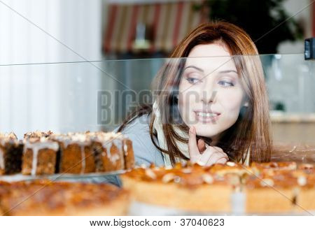 Woman in scarf looking at the bakery showcase full of different pieces of pies
