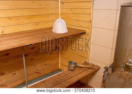 Bath Accessories In The Interior Of The Russian Bath. Cap, Wooden Ladle On A Background Of A Log Wal