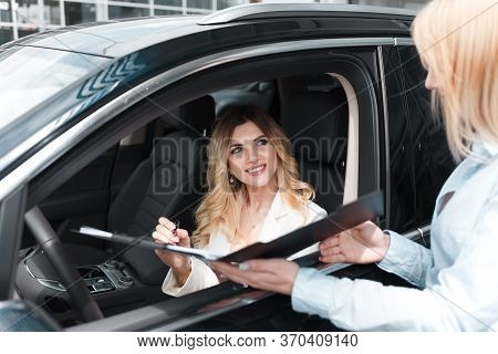Beautiful Woman Signs A Car Dealership Agreement. Business Lady In A Auto Dealership Buys A New Car