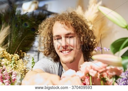Young florist as trainee in flower shop between many cut flowers