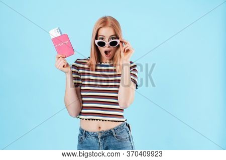 Image of astonished girl in sunglasses expressing surprise and holding passport with tickets isolated over blue background