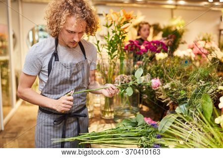 Young florist or trainee in flowers tying for a bunch of flowers