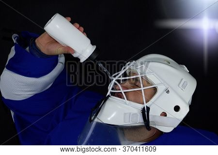 Hockey Goalie Drinks Water.detail Of A Male Face In A White Goalie Hockey Mask.this Is A Detail Hock