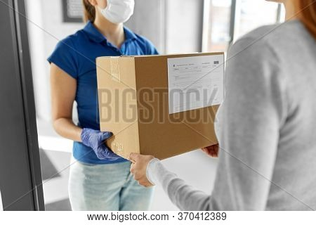 health protection, safety and pandemic concept - delivery woman in face protective mask and gloves giving parcel box to female customer at office