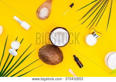 Top View Organic Natural Cosmetics For Face And Body Skincare With Coconut Oil On Yellow Background.