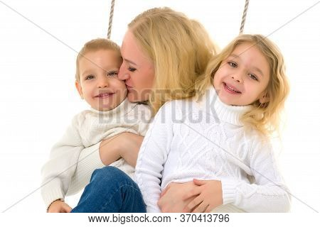 Family Of Mother And Two Kids Sitting Together On Rope Swing, Smiling Mom Hugging And Kissing Her Li