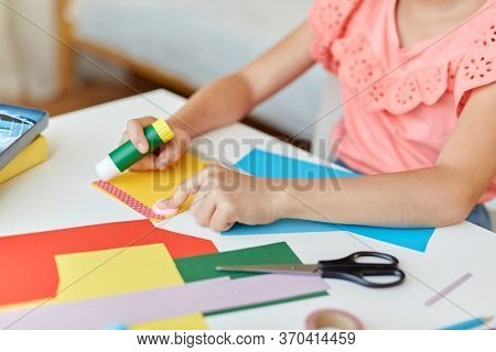 childhood, creativity and hobby concept - close up of creative girl making greeting card and sticking paper stripe with glue stick at home