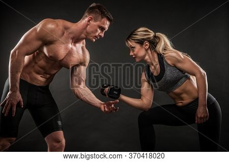 Fitness in gym, sport and healthy lifestyle concept. Couple of athletic man and woman showing their trained bodies on dark background. Two bodybuilder models standing and demonstrating tight muscles.