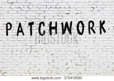 White Brick Wall With Inscription Patchwork Handwritten With Black Paint