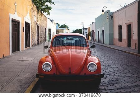 Merica, Yucatan, Mexico - 28 October 2018 - Front Of Red Oldtimer Volkswagen Beetle In The Colonial