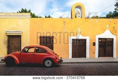 Merica, Yucatan, Mexico - 28 October 2018 - Red Oldtimer Volkswagen Beetle In The Colonial Historica