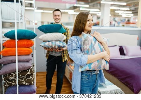 Love couple holds pillows in furniture store