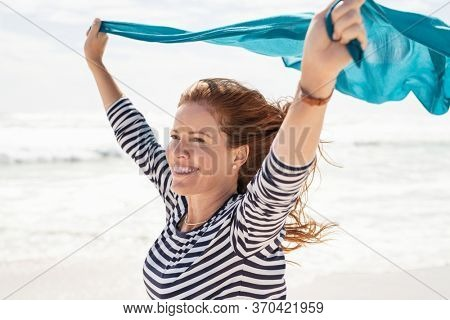 Smiling mature woman holding blue scarf over head while walking at beach. Happy active and healthy woman enjoying summer vacation at sea. Middle aged lady running at seashore with blue fabric.