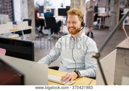 Portrait of consultant agent man in call center smiling. Happy customer support agent working with headset while sitting at his workstation. Smiling telephone operator using computer in open office.