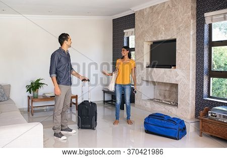 Young indian couple feeling excited on moving in new house. Young man and woman arrive in the holiday house booked online. Middle eastern couple with luggage checking their place for vacation.
