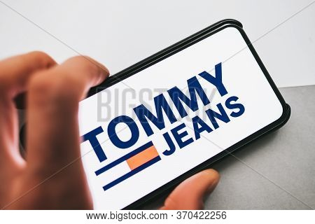 Iphone With Tommy Jeans Logo On The Screen. Black And Gray Background . High Quality Photo