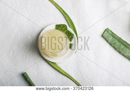 Fresh Aloe Vera Juice On A White Plate Surrounded By Aloe Leaves, Top View With Space For Text. Natu