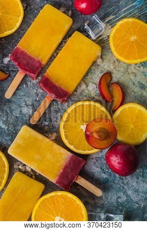 Close Up Of Orange And Plum Popsicles On A Grey Background, Top View. Fruit Popsicle/ice Cream With