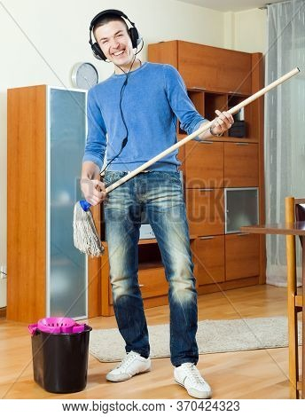 Happy Man Washing Floor With Mop In Living Room At Home.