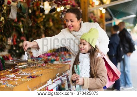 Smiling Mother With Positive Daugther In Christmas Market. Focus On Girl