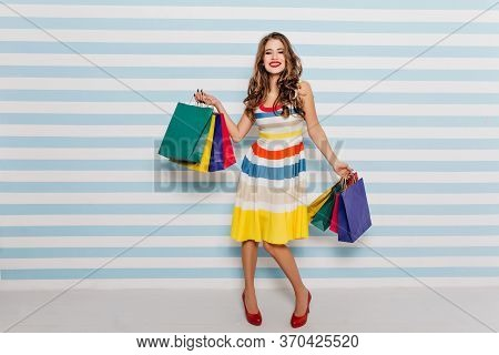Full-length Portrait Of Joyful Girl In Red Shoes Dancing With Purchases On Striped Background. Indoo