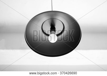Сhandelier Black Hangs Down From A Ceiling. White Ceiling. The Bulb In A Chandelier Doesn't Burn.