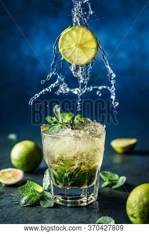Fresh Mojito Cocktail With Lime, Mint And Ice In Glass On Dark Blue Background. Studio Shot Of Drink