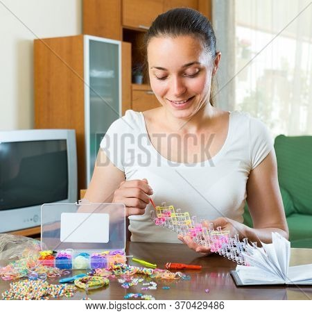 Smiling Woman Makes Bracelets With Elastic Rainbow Loom Bands.