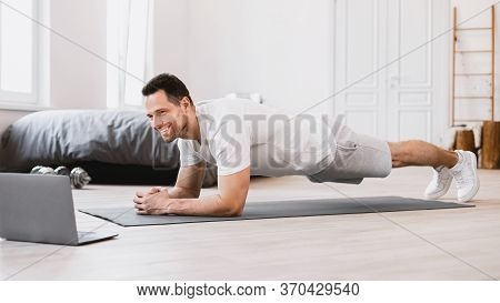 Home Training. Man Exercising At Laptop Doing Plank During Online Workout Indoors. Panorama