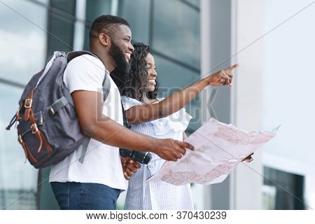 That Way. Black Couple Of Travellers Checking Route On Their City Map While Standing Near Airport Af