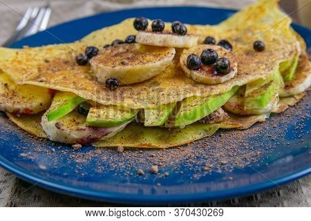 Tasty Pancakes With Bananas, Blueberries, Avocado And Honey On Blue Plate. Closeup View. Homemade Pa