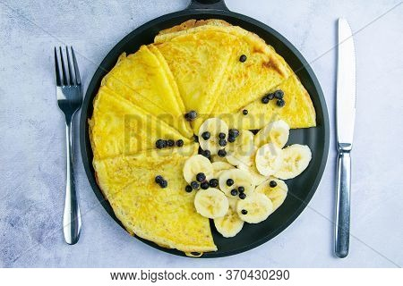Tasty Pancakes With Bananas And Blueberries On Black Frying Pan. Closeup View. Homemade Pancakes. Pa