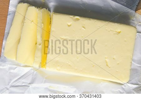 Piece Of Unwrapped Butter On Wooden Table. Top Views, Close-up.