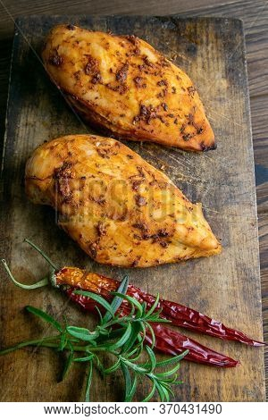 Baked Chicken Breast With Peper And Rosemary On Wooden Cutting Board On Wooden Table. Top Views, Clo