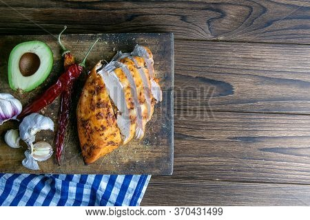 Baked Chicken Breast With Peper, Rosemary, Avocado And Garlic On Wooden Cutting Board On Wooden Tabl